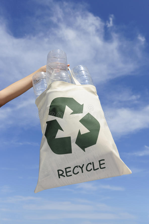 Recycling: hand holding bag with plastic bottles stock photo