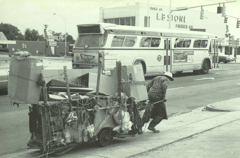 The Recycling Man. The city is Charlotte, NC. The Recycling Man is heading south on Tryon Street. Sedulously pulling his loaded cart. The date is 1970. It`s royalty free stock photo