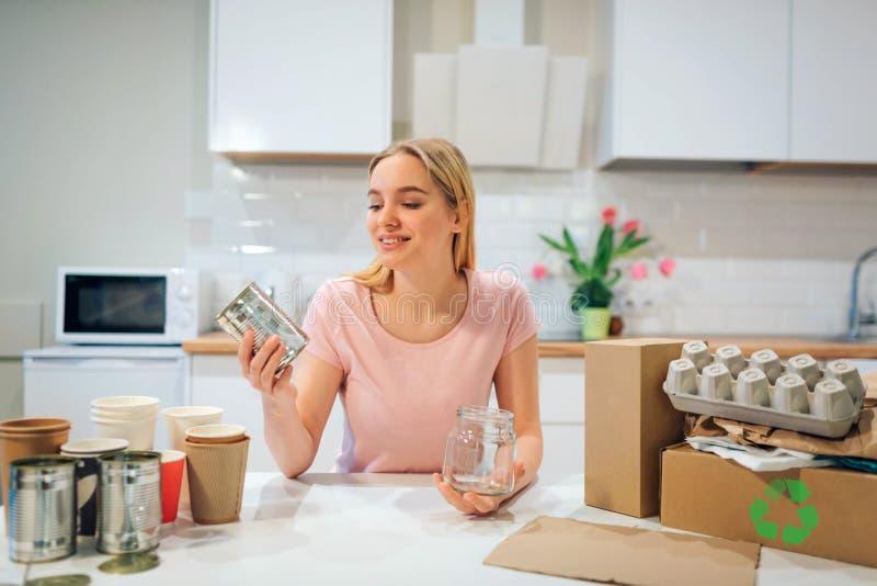 recycling A mulher de sorriso nova está classificando garrafas de vidro e latas vazias do metal ao sentar-se na tabela com o outr fotografia de stock