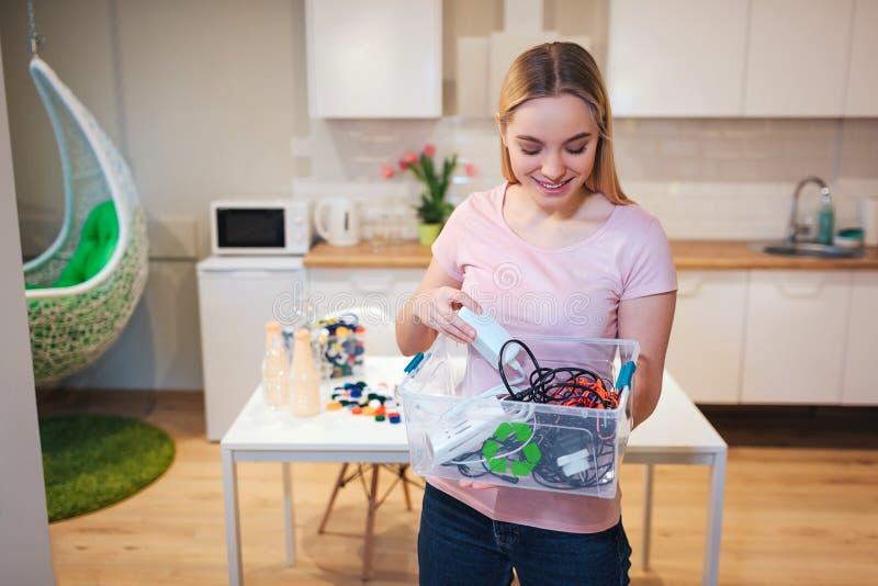 recycling A mulher de sorriso nova que guarda o desperdício eletrônico no recipiente com verde recicla o ícone no fundo da cozinh foto de stock royalty free