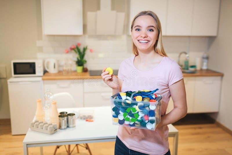 recycling A mulher de sorriso nova que guarda tampas plásticas no recipiente com verde recicla o ícone no fundo da cozinha foto de stock
