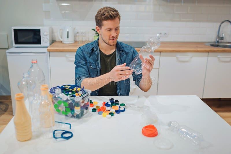 recycling O homem de sorriso novo está classificando a garrafa e tampas plásticas vazias ao sentar-se na tabela imagem de stock royalty free