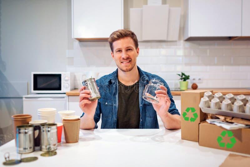 recycling O homem de sorriso novo está classificando garrafas de vidro e latas vazias do metal ao sentar-se na tabela com o outro imagens de stock royalty free