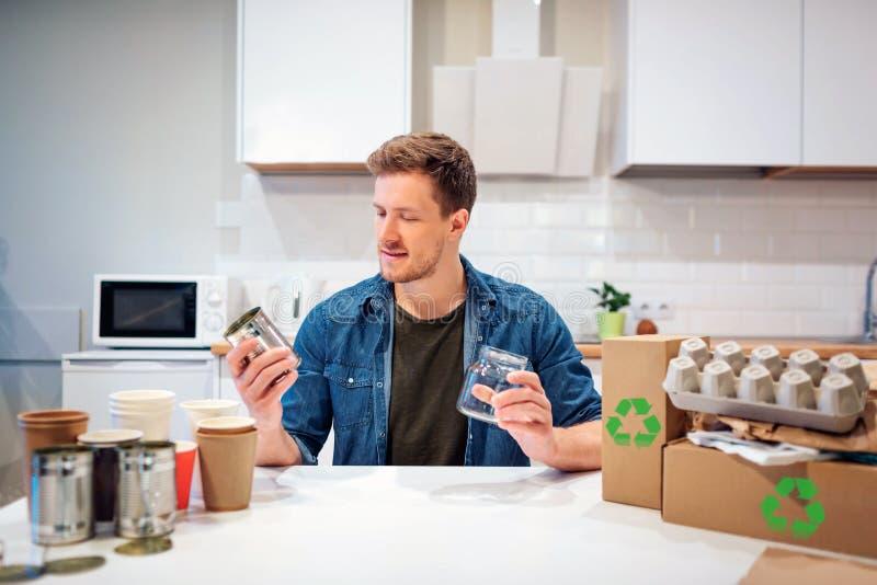 recycling O homem de sorriso novo está classificando latas do metal e as garrafas de vidro ao sentar-se na tabela com o outro des imagens de stock