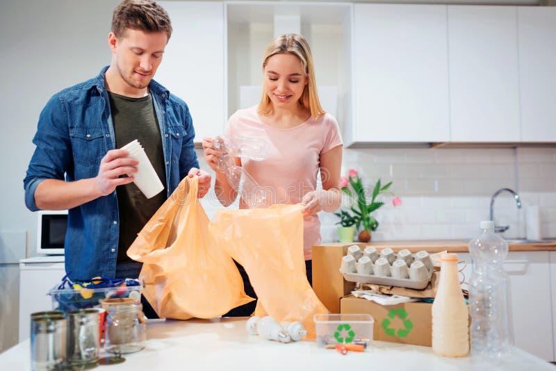 recycling Pares novos responsáveis que põem o plástico e o papel vazios em sacos de lixo quando estar perto da tabela se encheu foto de stock