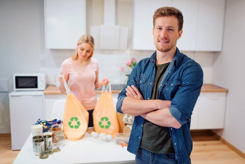 recycling Posição de sorriso nova do homem após a reciclagem quando sua amiga que guarda sacos de lixo com reciclar o símbolo em imagens de stock royalty free