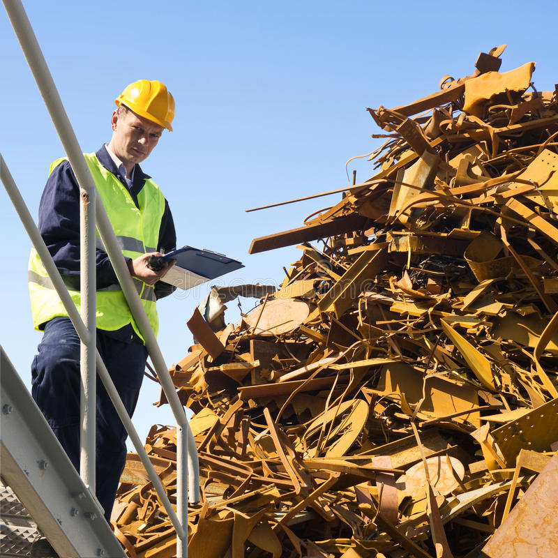 Recycling specialist. Metal scrap heap detail against a clear blue sky royalty free stock images