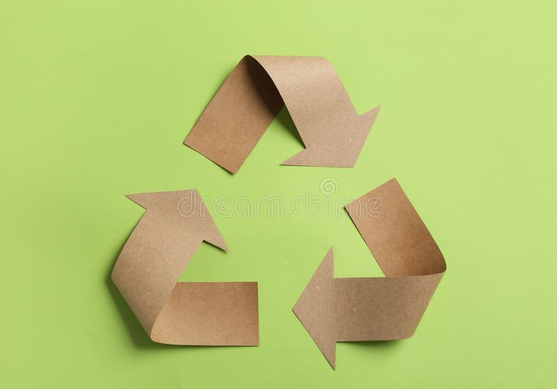 Recycling symbol cut out of kraft paper on green background. Top view royalty free stock images