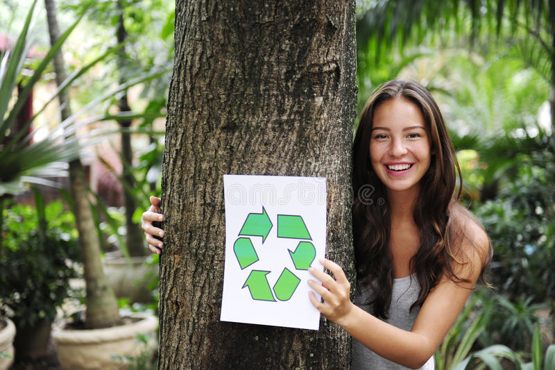 Recycling: woman in forest with recycle sign stock photography