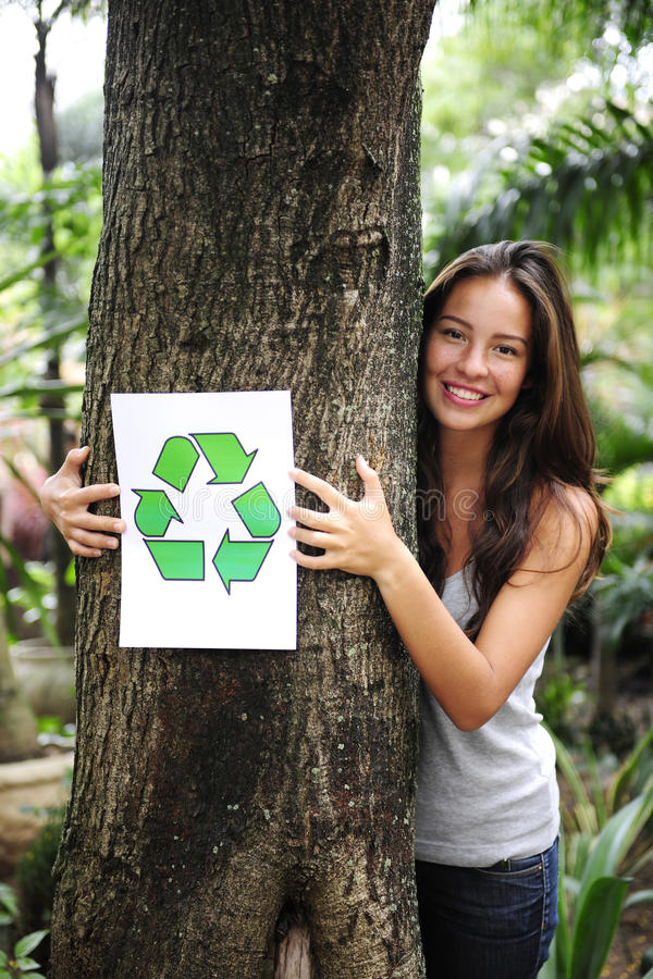 Recycling: woman in the forest with recycle sign stock images