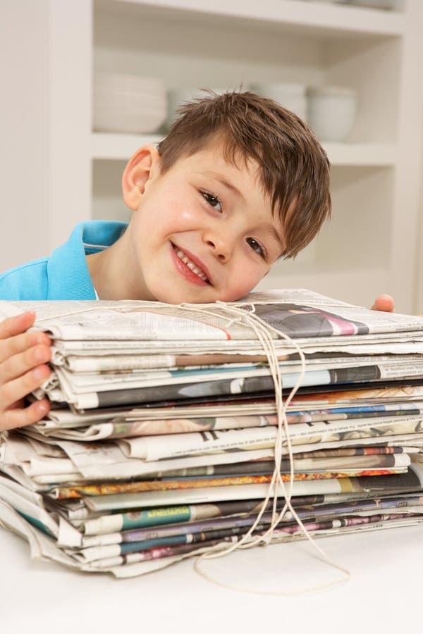 recyling年轻人的男孩家庭报纸 免版税库存照片