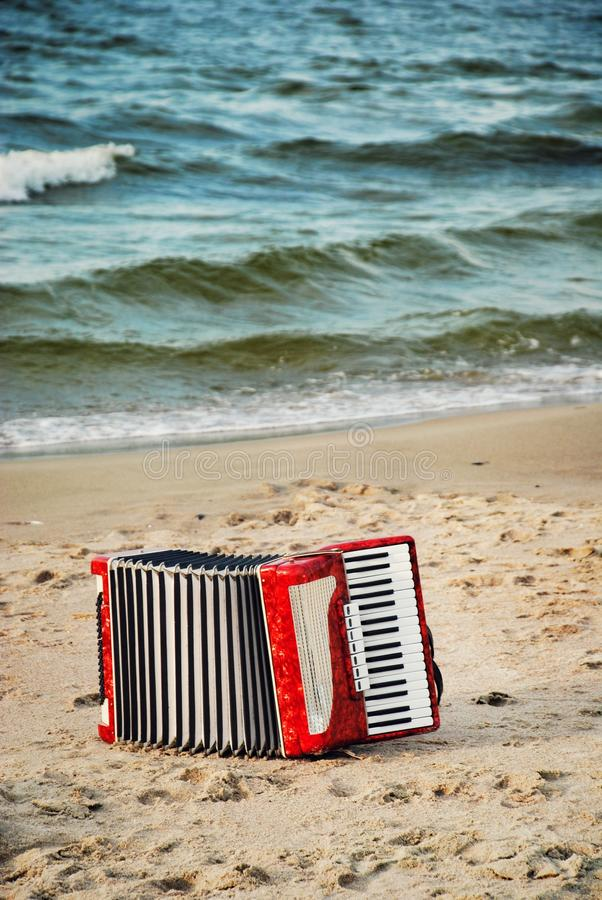 A red accordion on a beach royalty free stock photos