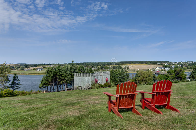 Red Adirondack Chairs. Two red adirondack chairs overlooking a waterfront view royalty free stock photos