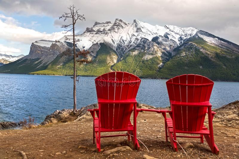 Red Adirondack Chairs at Lake Minnewanka in Banff National Park. Red Adirondack Chairs and Dramatic Stormy Sky Landscape at Lake Minnewanka on Windy Autumn Day royalty free stock images
