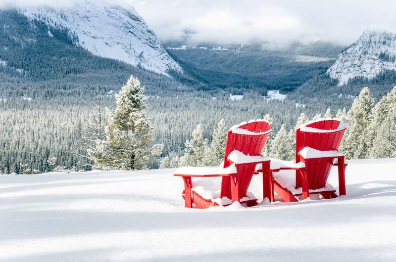 Red Adirondack Chairs in front of a Snowy Valley. Two Snow Covered Red Adirondack Chairs in front of a Snowy Forested Valley on a Winter Day. Banff National Park stock images