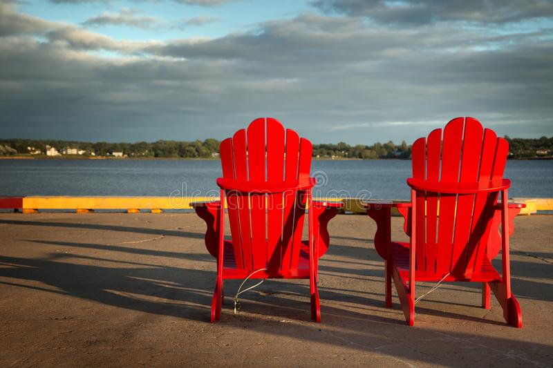 Red adirondack chairs in front of water. 2 red Adirondack chairs in front of the ocean in Prince Edward island royalty free stock photos
