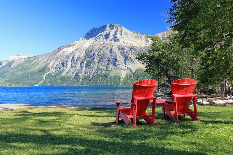 Red Adirondack Chairs at Waterton Lakes National Park, Alberta. Two red Parks Canada Adirondack Chairs are sitting at the shore of Middle Waterton Lake with a royalty free stock image