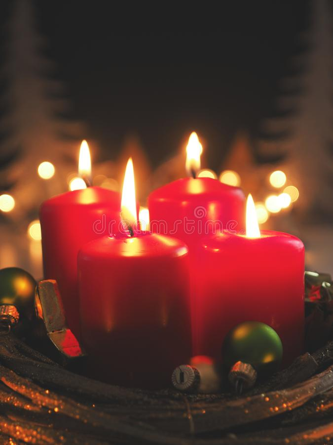 Red Advent candles. Fourth Advent candle burning with decoration in a dark room, space for text or image stock photos