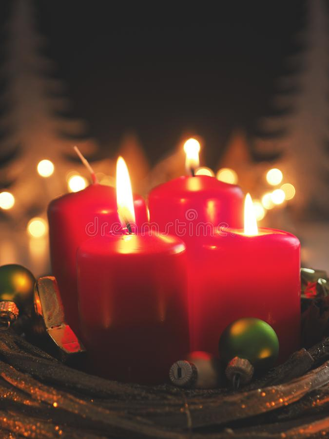 Red Advent candles. Third Advent candle burning with Christmas decoration in a dark room, space for text or image royalty free stock images