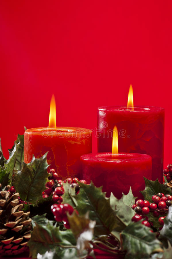 Red advent wreath with candles. Red advent flower arangement with burning candles stock photo