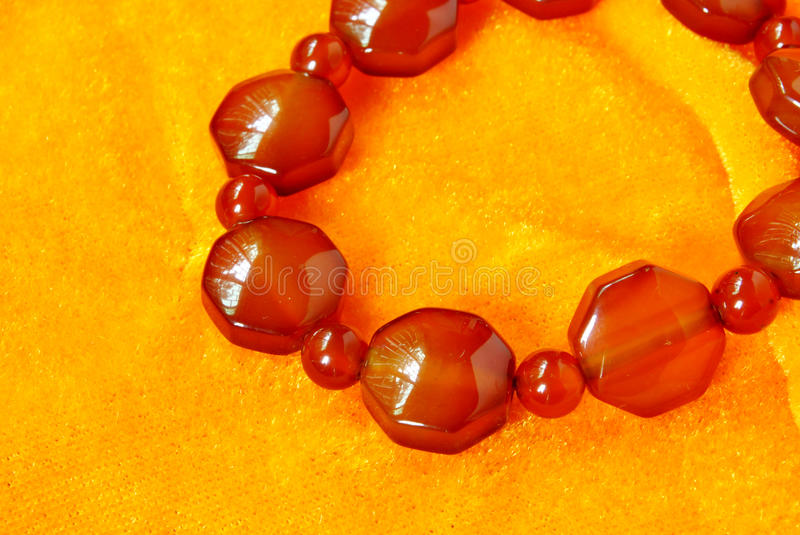 Red agate beads jewelry accessories. Golden velvet background red agate beads jewelry accessories stock image