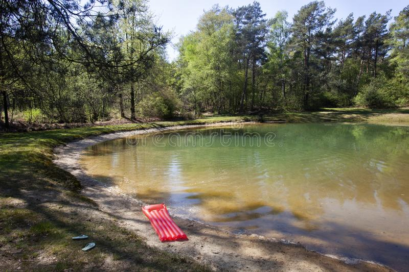 Red air mattress and blue flip flops near a fen. In the Netherlands royalty free stock images