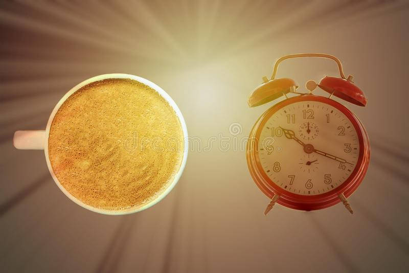 An alarm clock and a coffee with the sun in the background stock image