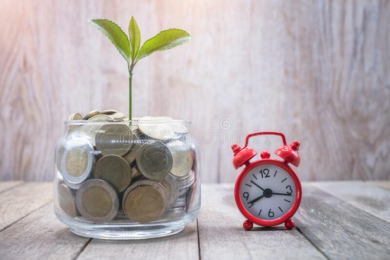 A red alarm clock on a coin Financial concepts, savings, investments in finance, accounting and the stock market Use time that`s. Worth the investment stock photography