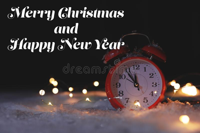 Red alarm clock with fairy lights on snow and message MERRY CHRISTMAS AND HAPPY NEW YEAR against dark background. royalty free stock images