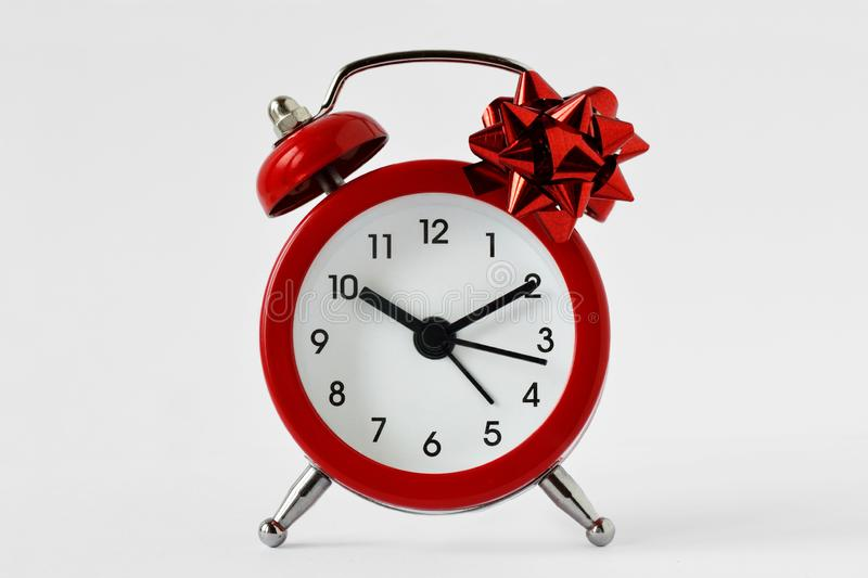 Red alarm clock with gift bow on white background - The gift of time concept; time for gift giving concept stock photos