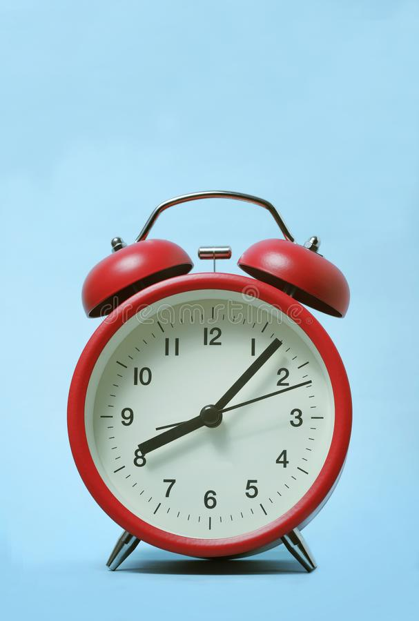 Red alarm clock on light blue color background. stock photo