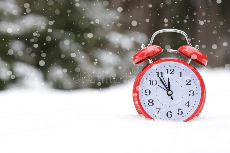Red alarm clock outdoors on snowy winter day. stock photography