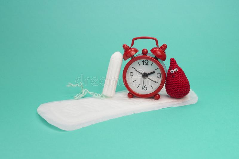 Red alarm clock, smile crochet blood drop, daily menstrual pad and tampon. Menstruation sanitary woman hygiene. Woman critical day. S, gynecological menstruation royalty free stock photos