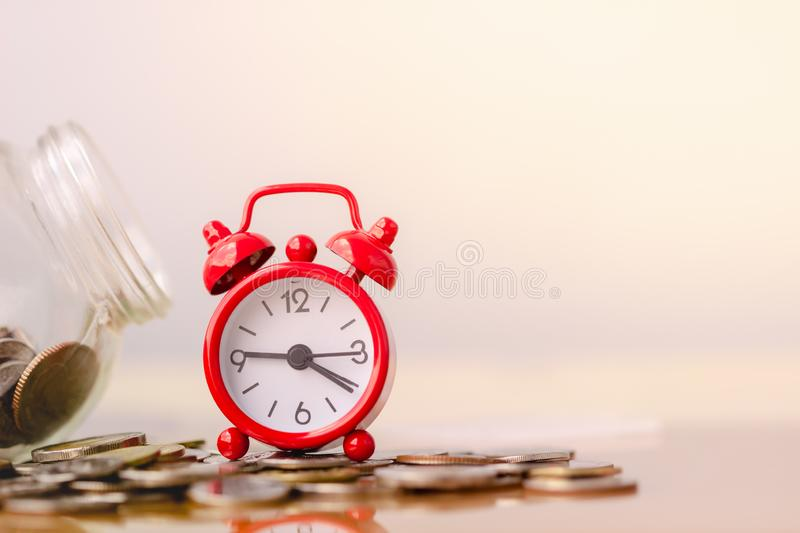 Red alarm clock on stack of coins in concept of savings and money growing or energy save. Business investment growth concept. Money saving and Investment royalty free stock photos