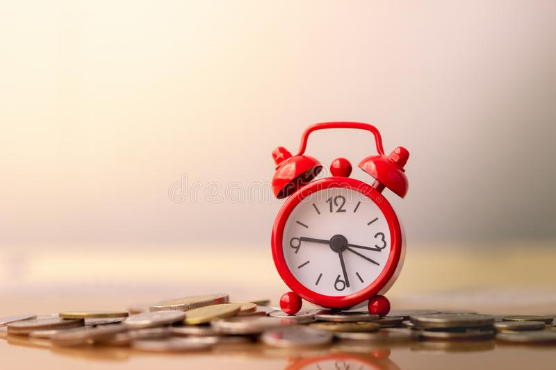 Red alarm clock on stack of coins in concept of savings and money growing or energy save. Business investment growth concept. money saving and Investment stock photography