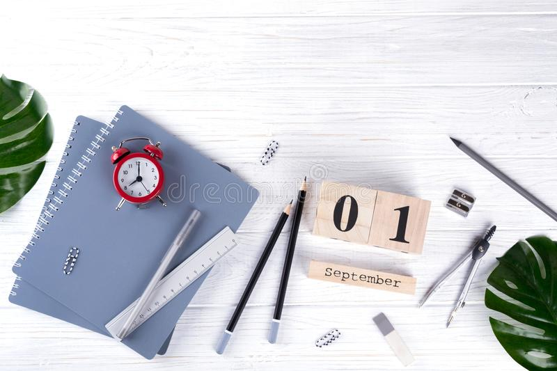 Red alarm clock and supplies, wooden calendar with date 1st September. on white desk. Back to school concept. stock images