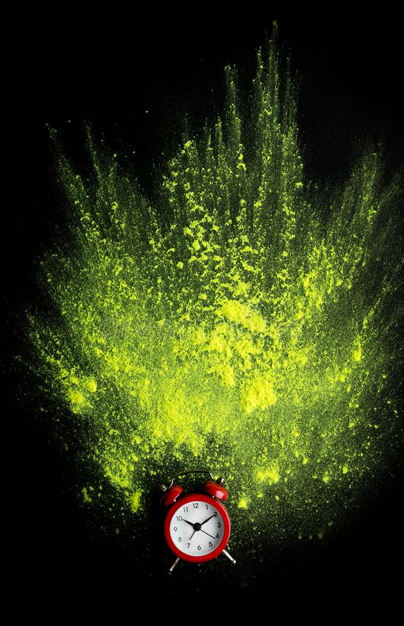 Red alarm clock with yellow holi powder explosion on black royalty free stock images