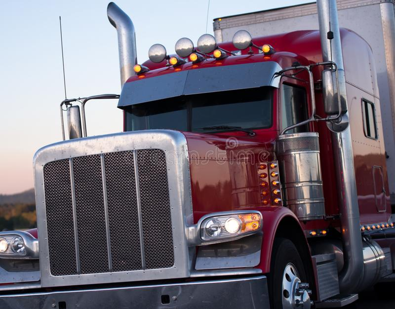 Red American long haul big rig semi truck with accessories. Classic powerful American pro big rig semi truck in dark red with shiny grille, high chrome pipes and royalty free stock photography