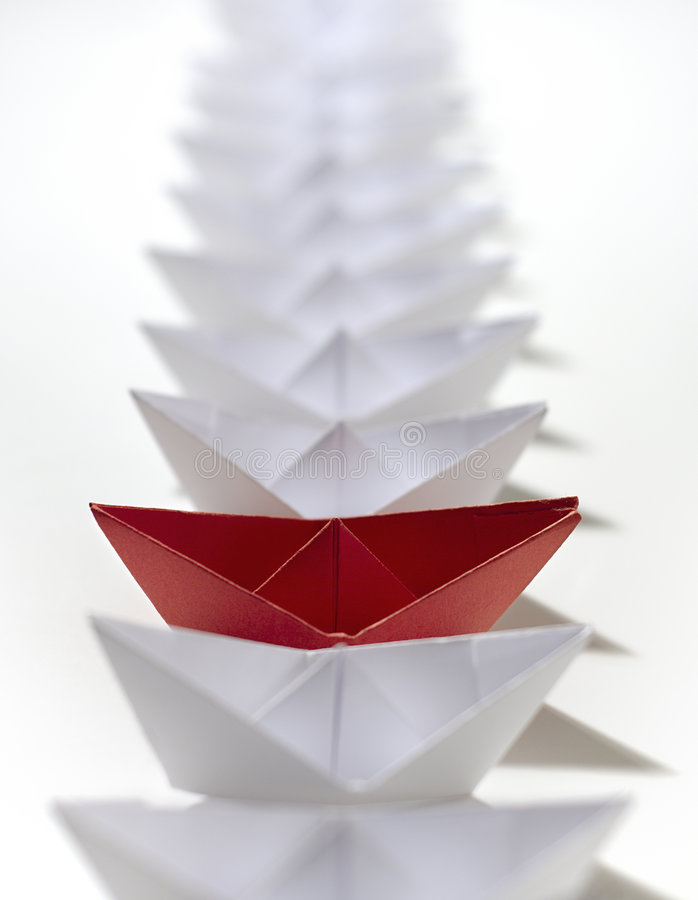 Red amongst white paper ships stock image