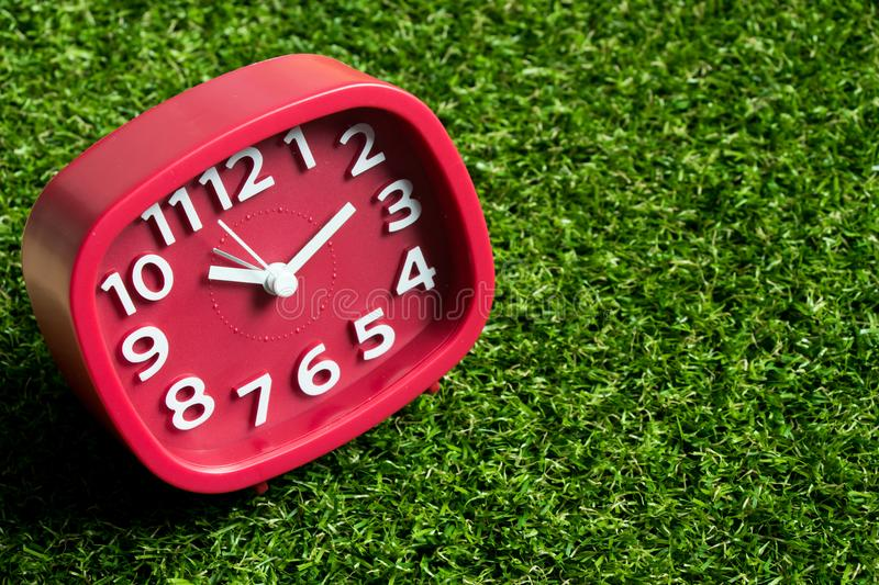 Red analog clock on artificial green grass. Background royalty free stock image