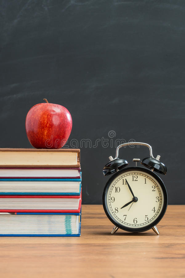 Red apple and alarm clock on school desk for back to school royalty free stock image