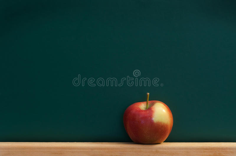 Red apple on chalkboard royalty free stock image