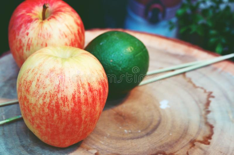 Red apple and green lemon on cutting wooden board, Thailand kitchen tools royalty free stock images