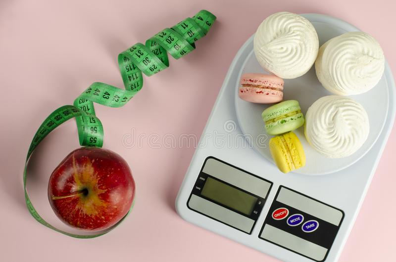 Red apple with green measuring tape, digital kitchen scales with macarons. And meringues on pink background. Weight loss and slimming treatment concept. Top royalty free stock images