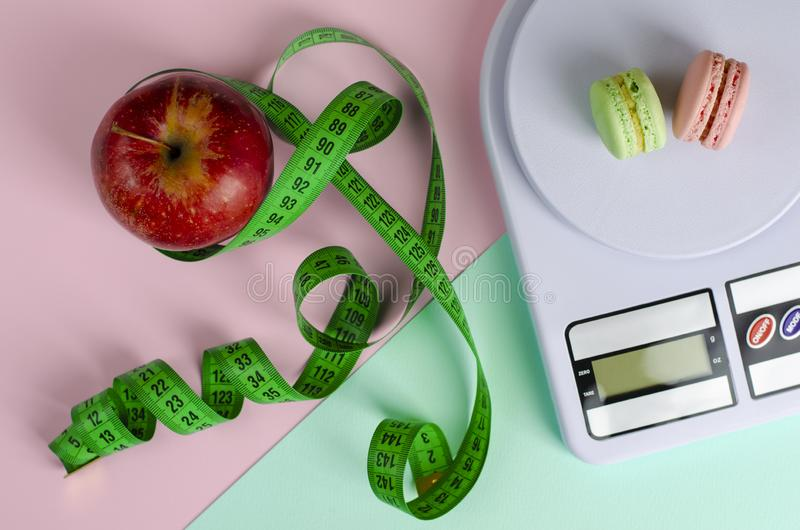 Red apple with green measuring tape, digital kitchen scales with macarons. On pink and mint background. Weight loss and slimming treatment concept. Top view. No stock photo