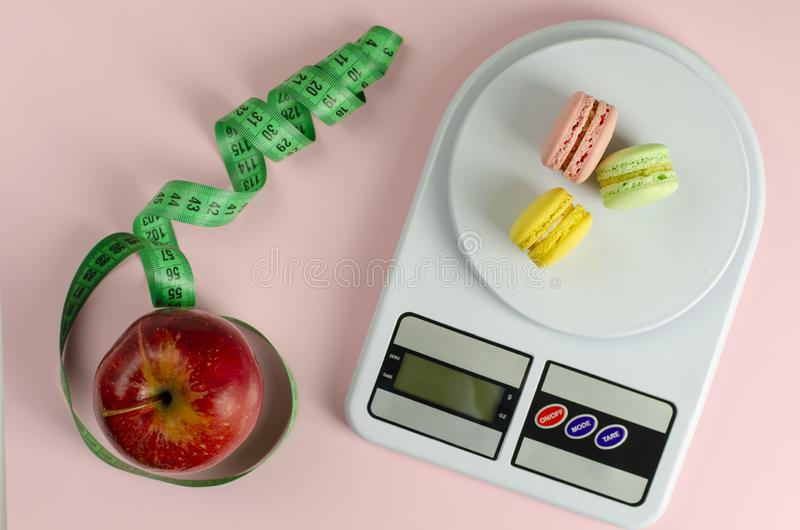 Red apple with green measuring tape, digital kitchen scales with macarons. On pink background. Weight loss and slimming treatment concept. Flat lay. Top view royalty free stock photo