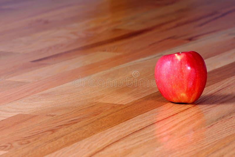 Red Apple on Hardwood Floor. A shiny red apple on a hardwood floor stock photo