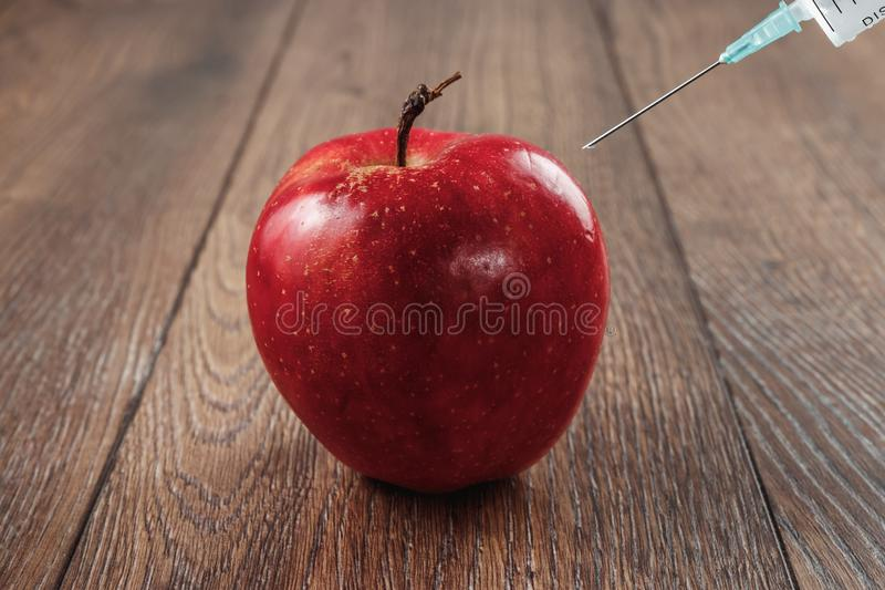 Red apple injecting a needle or syringe and chemical pesticides on a wooden background. Specific pesticide residues in apples, stock image