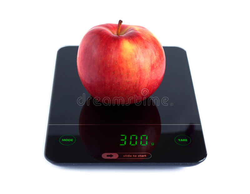 Red apple on kitchen scales isolated on white closeup. Big tasty red apple on kitchen scales isolated on white background. Front view closeup royalty free stock photos
