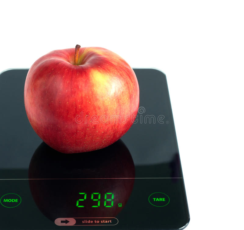 Red apple on kitchen scales isolated on white closeup. Big tasty red apple on kitchen scales isolated on white background. Front view closeup stock photography